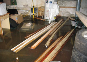 A severely flooding basement in Park City, with lumber and personal items floating in a foot of water
