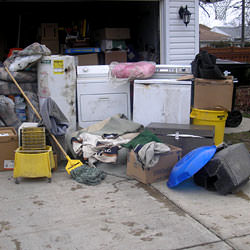 Soaked, wet personal items sitting in a driveway, including a washer and dryer in Layton.